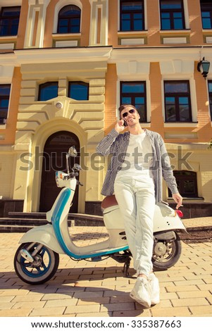 Young handsome man standing near a motorbike talking on the phone - stock photo