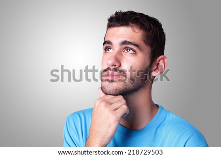 young handsome man student think and doubt isolated over gray background, caucasian - stock photo