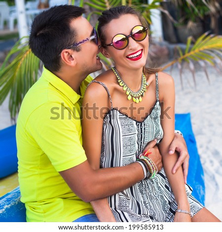 Young handsome man tell funny story to his pretty stylish girlfriend, sitting  hugs and having fun together at beautiful sunny beach. - stock photo