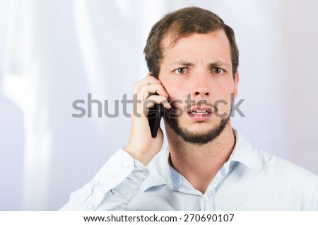 young handsome man using cell phone talking looking worried - stock photo