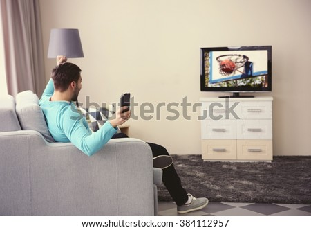 Young handsome man watching TV on a sofa at home - stock photo