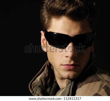 Young handsome man wearing dark sunglasses - stock photo