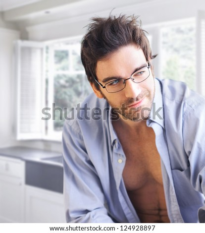 Young handsome man wearing fashion eyeglasses in bright modern interior - stock photo
