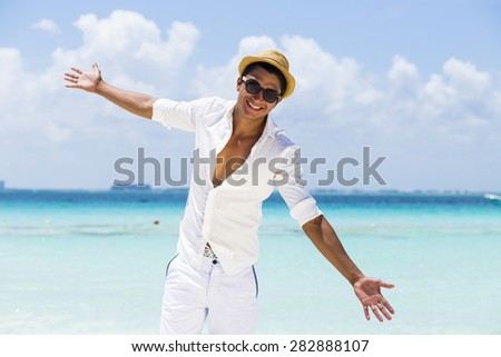 Young handsome man wearing white fresh clothes in a sunny day at the beach - stock photo