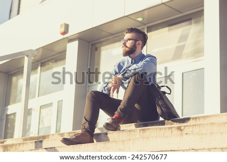Young, handsome man with a briefcase, dressed in the style of hipster, sitting on the stairs - stock photo