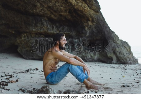 young handsome man with beard and mustache hipster style,in jeans on the ocean beach.Outdoor fashion portrait,close up,posing on the beach in denim,the bearded man. - stock photo