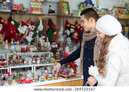 Young handsome man with beautiful girlfriend at counter of X-mas market. Focus on man - stock photo