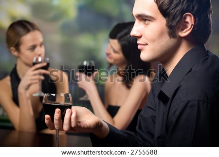 Young handsome man with glass of red-wine and two attractive women at celebration or party - stock photo