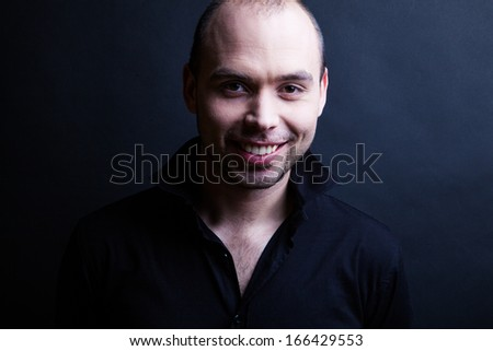 Young handsome man with great smile on the black background - stock photo
