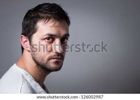Young handsome man with serious expression on dark background - stock photo