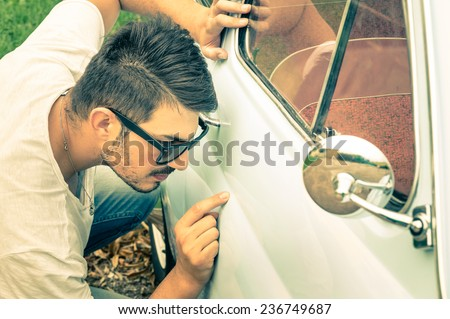 Young handsome man with sunglasses inspecting a vintage car body at second hand trade - Passion and transportation lifestyle of a retro classic vehicles collector - stock photo