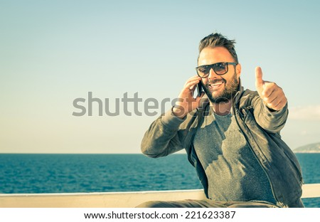 Young handsome man with thumbs up during a phone call with his smartphone - Concept of technology connected with traveller lifestyle - Male model showing success for a mobile telephony company - stock photo