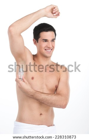 Young handsome men applying deodorant on armpits. nude man standing on white background and smiling - stock photo