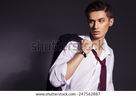 Young handsome men in suit shirt and red tie wear watches looking sideways. dark background. indoors. copy space - stock photo