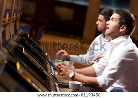 young handsome men playing the slot machine in a casino - stock photo