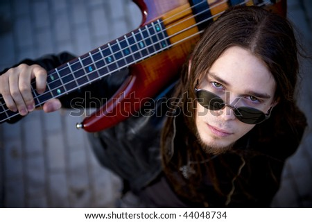 Young handsome musician in urban background - stock photo