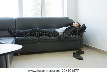 Young Handsome Office Man Lying on the Gray Couch at Lounge Area During Work Break Hours. - stock photo