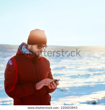 Young handsome polar north pole scientist making researches with mobile phone standing and freezing in winter on snow field evening in red warm jacket and hat on blue clear sky background  - stock photo