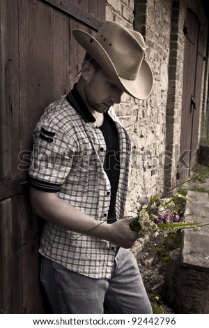 Young handsome sad man in cowboy hat standing with bunch of flowers - stock photo