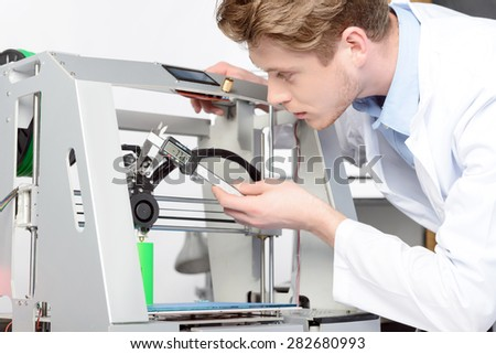 Young handsome scientist measuring something with calipers in 3D-printer, wearing white lab coat in laboratory - stock photo