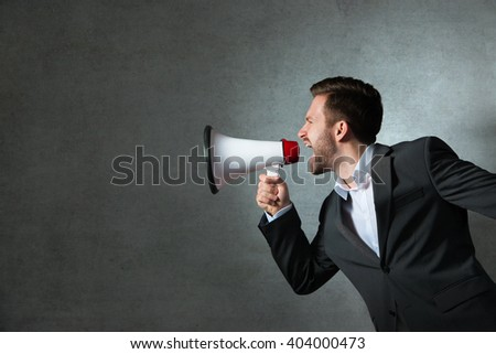 Young handsome shouting man using megaphone over grey background - stock photo