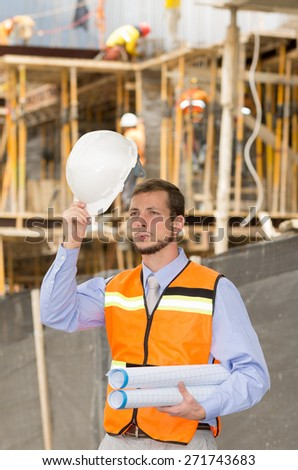 young handsome smiling architect supervising a construction holding helmet - stock photo