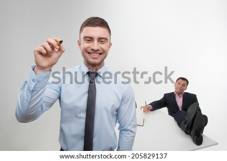Young handsome smiling businessman holds marker writing, drawing something in the air, his chief relaxing with his feet on the desk on background isolated on white - stock photo