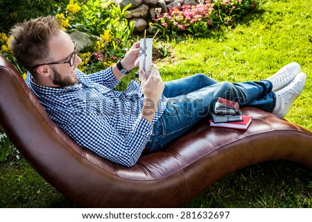 Young handsome smiling man in casual clothes & glasses with gift card relax in luxury sofa in summer garden. - stock photo