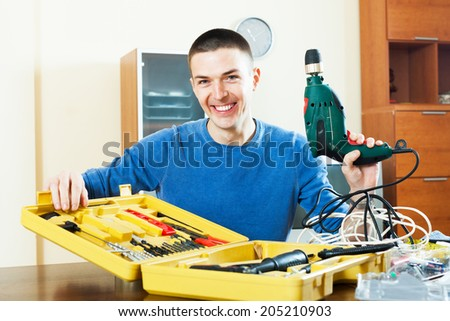Young handsome smiling man sitting by table with toolbox holding drill in hand - stock photo