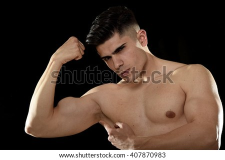 young handsome sport man posing with strong naked torso looking cool and defiant with bent arm pointing biceps muscle in healthy lifestyle and gym club bodybuilding advertising concept - stock photo
