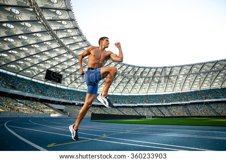 Young handsome sportsman running on racetrack outdoors. Fit sporty man is at large nice modern stadium - stock photo
