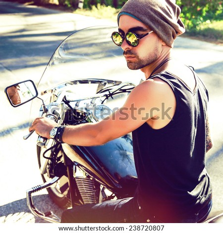 Young handsome stylish man riding bike, wearing hat and sunglasses, brutal rock n roll style. Instagram bright colors. - stock photo