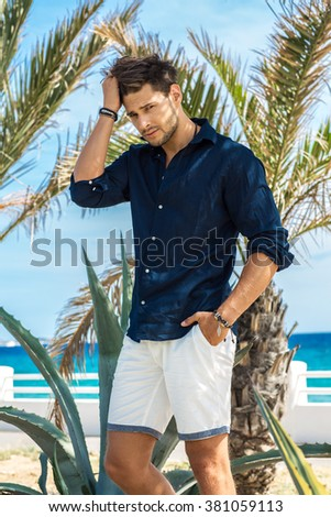 Young handsome tanned model posing under the palms  - stock photo