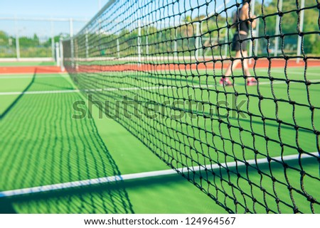 Young handsome woman playing tennis on court during hot sunny day in Cape town - stock photo