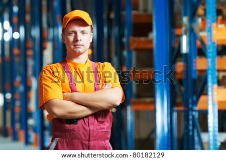 young handsome worker man in uniform in front of warehouse rack arrangement stillages - stock photo
