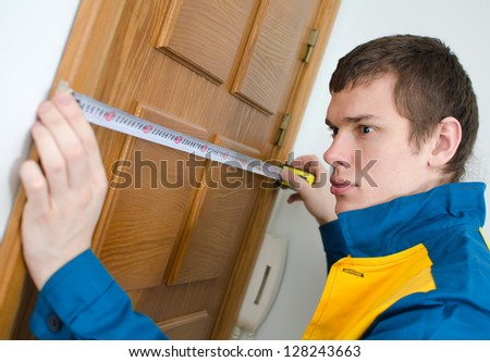 Young handyman in uniform working with measure tape - stock photo