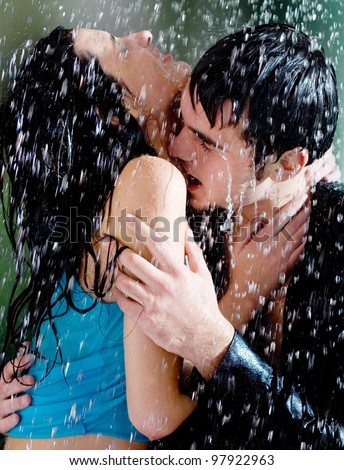 Young happy amorous couple hugging and kissing under a rain - stock photo