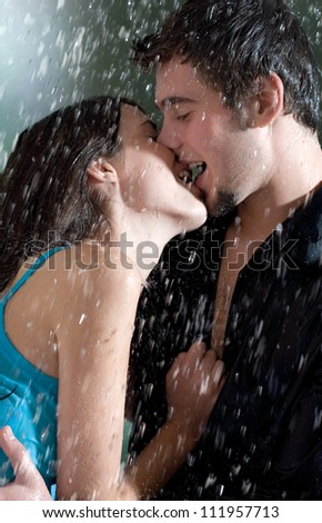 Young happy amorous couple hugging and kissing under a rain, outdoors - stock photo