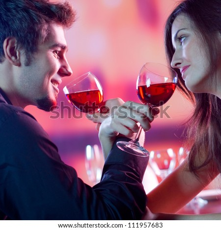 Young happy amorous couple with glasses of redwine on romantic date at restaurant - stock photo