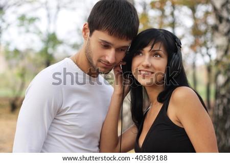 Young happy amorous couple with headphones - stock photo