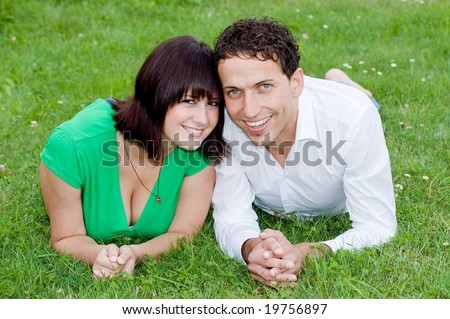 Young, happy and smiling couple in a park. - stock photo
