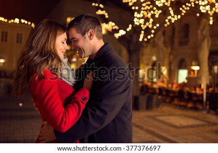 Young happy attractive amorous couple embracing  and kissing outdoor - stock photo