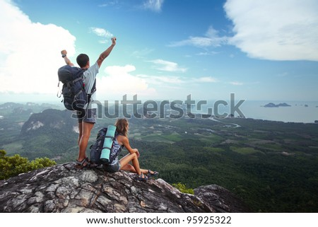 Young happy backpackers on top of a mountain enjoying valley view - stock photo