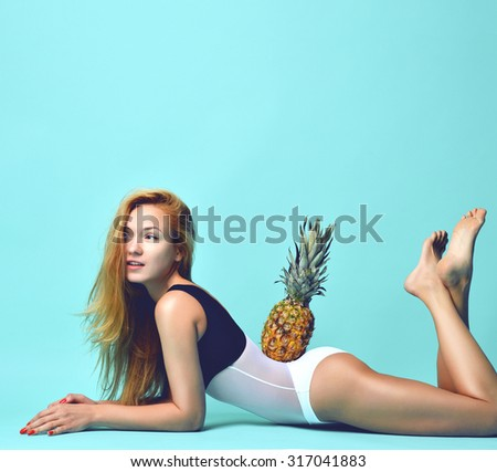 Young happy beautiful sexy woman posing laughing with pine apple fruit on blue background - stock photo