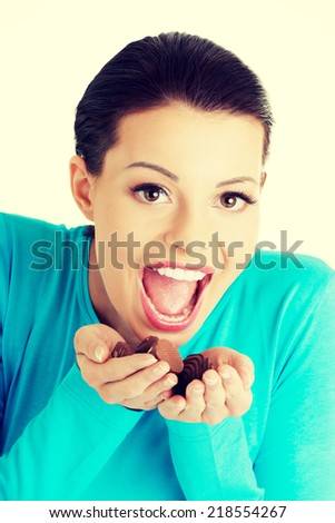 Young happy beautiful woman in casual clothes with hand full of chocolates - stock photo