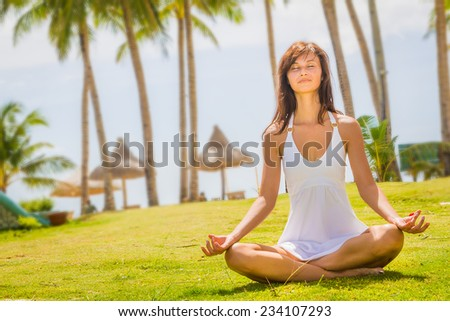young happy beautiful woman outdoor portrait, meditating on beach and sky background - stock photo