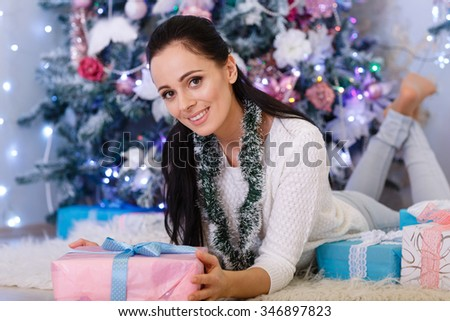 Young happy beautiful woman with gift boxes lies near Christmas tree in the room of the house. Merry Christmas and New Year. - stock photo