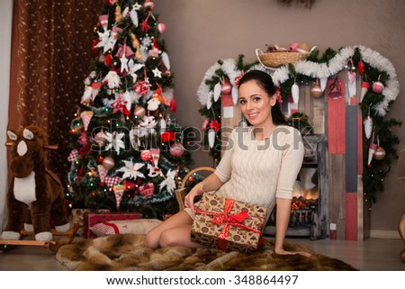 Young happy beautiful woman with gift boxes sits near Christmas tree in the room of the house. Merry Christmas and New Year. - stock photo