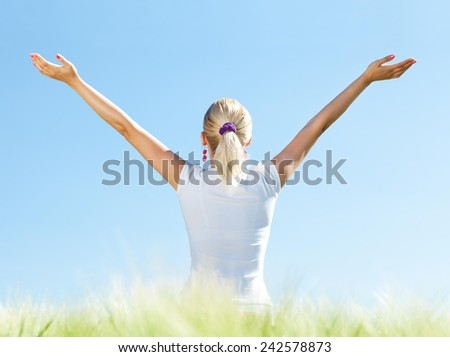 Young happy blond girl in a wheat field. - stock photo
