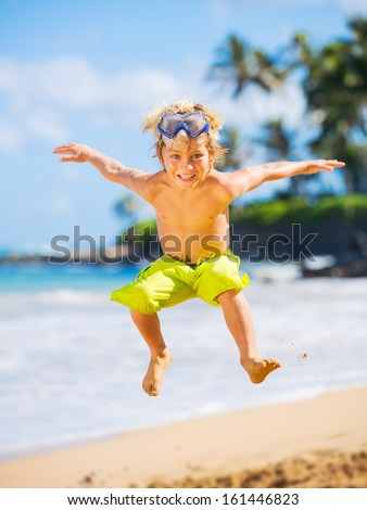 Young happy boy having fun on tropical beach, jumping into the air - stock photo